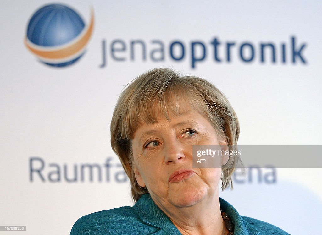 German Chancellor Angela Merkel looks on during her visit of Jena-Optronik GmbH (Ltd), a provider of opto-electronic instruments and sub-systems for space applications, on May 2 , 2013 in Jena, eastern Germany.