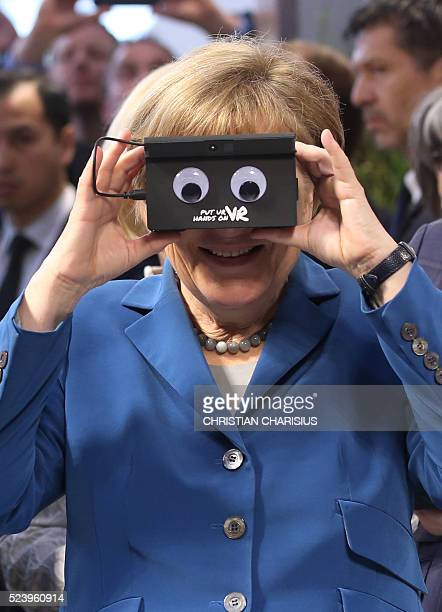 German Chancellor Angela Merkel looks through a device at the booth of German automation company ifm electronic as they tour the Hanover industrial...