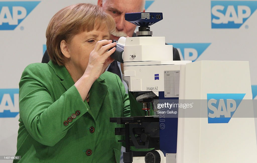 German Chancellor Angela Merkel looks through a microscope during an oncology presentaiton at the SAP stand on the first day of the CeBIT 2012 technology trade fair on March 6, 2012 in Hanover, Germany. CeBIT 2012, the world's largest information technology trade fair, will run from March 6-10, and advances in cloud computing and security are major features this year.