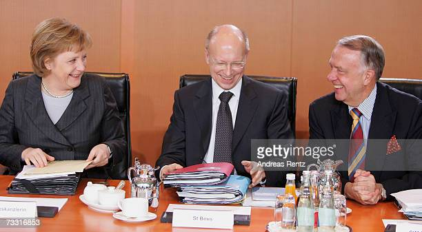 German Chancellor Angela Merkel looks to deputy Minister for Culture Bernd Neumann as State Secretary of the Chancellery Hans Bernhard Beus smiles...
