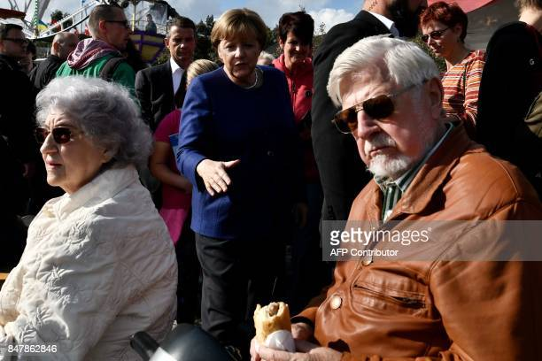 German Chancellor Angela Merkel makes her way to greet people at a fair as she continued on the election campaign trail in Stralsund on September 16...