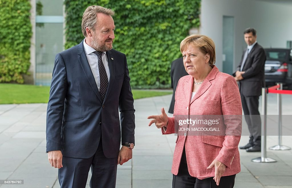 German Chancellor Angela Merkel (R) makes the number three with her hand as she and member of the Presidency of Bosnia and Herzegovina Bakir Izetbegovic wait for the two other members of the Bosnian Presidency during a welcoming ceremony at the chancellery in Berlin on June 30, 2016. / AFP / JOHN