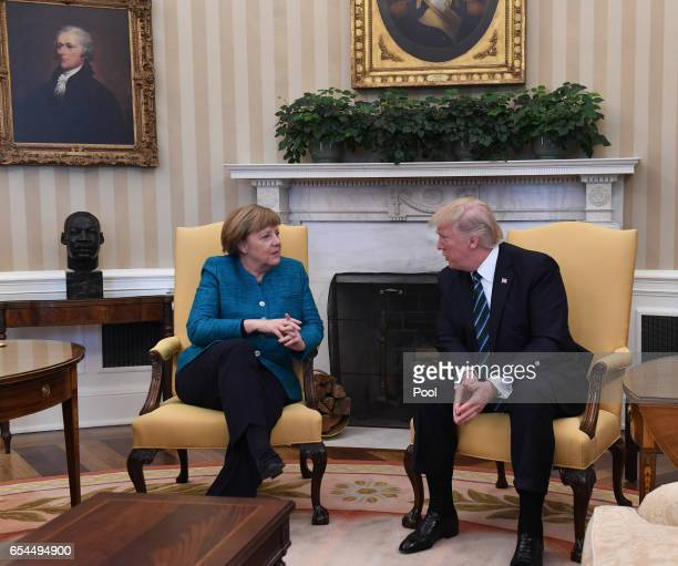 German Chancellor Angela Merkel meets with US President Donald Trump in the Oval Office of the White House on March 17 2017 in Washington DC This is...