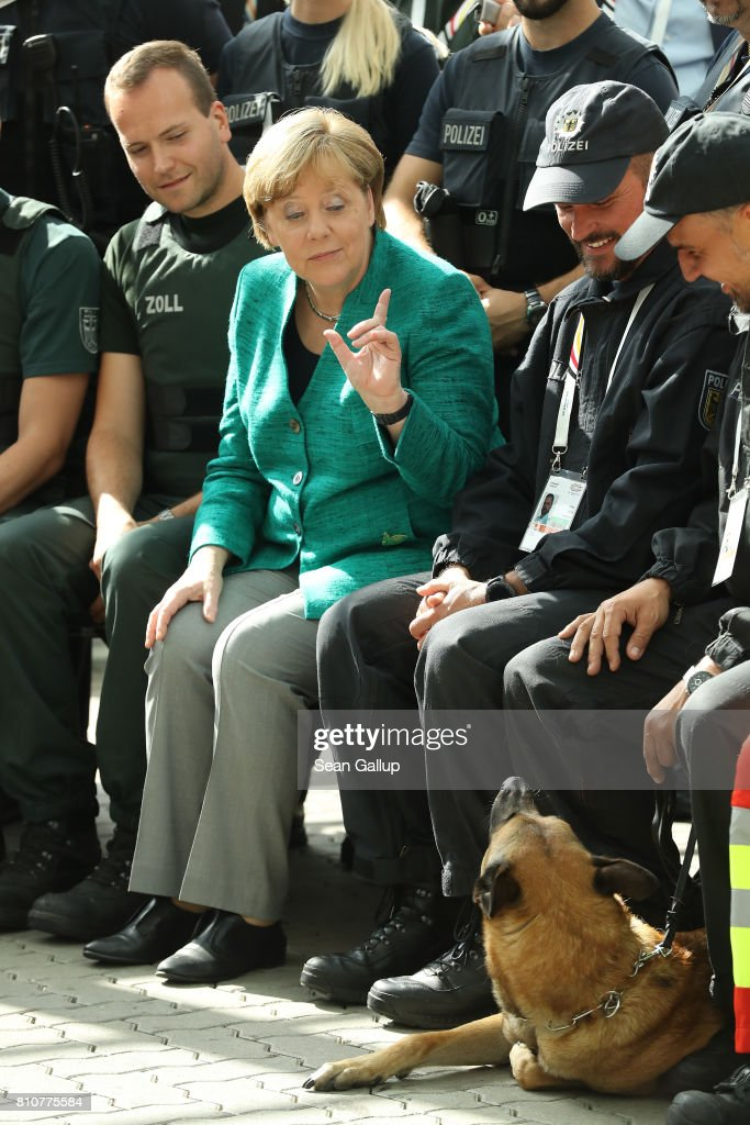 German Chancellor Angela Merkel motions to a police dog while thanking members of German law enforcement and emergency services at the conclusion of the G20 economic summit on July 8, 2017 in Hamburg, Germany. Severe rioting by anti-G20 activists that included looting, arson and physical attacks against police overshadowed the two-day summit.