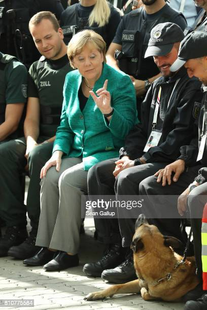 German Chancellor Angela Merkel motions to a police dog while thanking members of German law enforcement and emergency services at the conclusion of...
