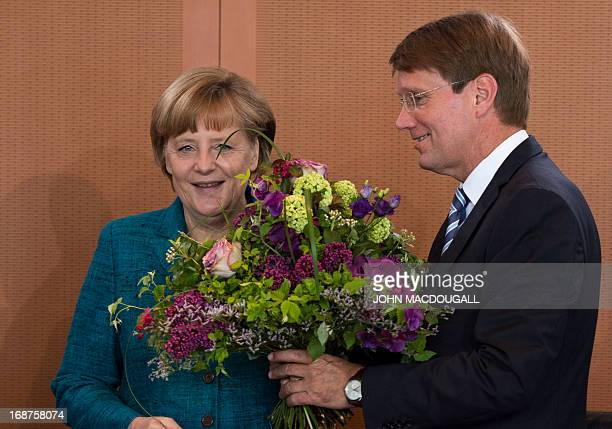 German Chancellor Angela Merkel offers a bouquet to German Chief of Staff Ronald Pofalla on the occasion of his birthday prior to a weekly cabinet...