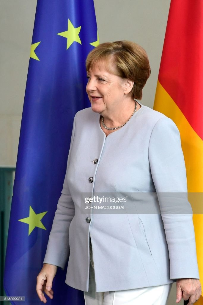 German chancellor Angela Merkel passes by the Eureopan Union flag after a press conference with Ukrainian Prime Minister at the Chancellery in Berlin on June 27, 2016. / AFP / John MACDOUGALL / ALTERNATIVE