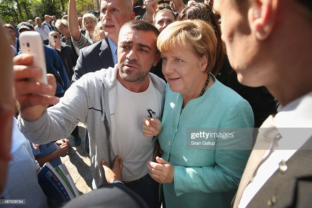 German Chancellor Angela Merkel pauses for a selfie with a migrant after she visited the AWO Refugium Askanierring shelter for migrants on September...