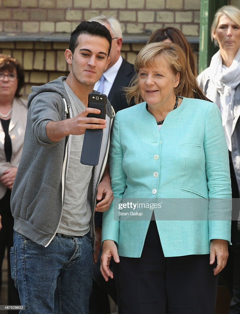 German Chancellor Angela Merkel pauses for a selfie with a migrant after she visited the AWO Refugium Askanierring shelter for migrants on September 10, 2015 in Berlin, Germany. Merkel visited several facilities for migrants today, including an application center for asylum-seekers, a school with welcome classes for migrant children and a migrant shelter. Thousands of migrants are currently arriving in Germany every day, most of them via the Balkans and Austria. Germany is expecting to receive 800,000 asylum applicants this year.