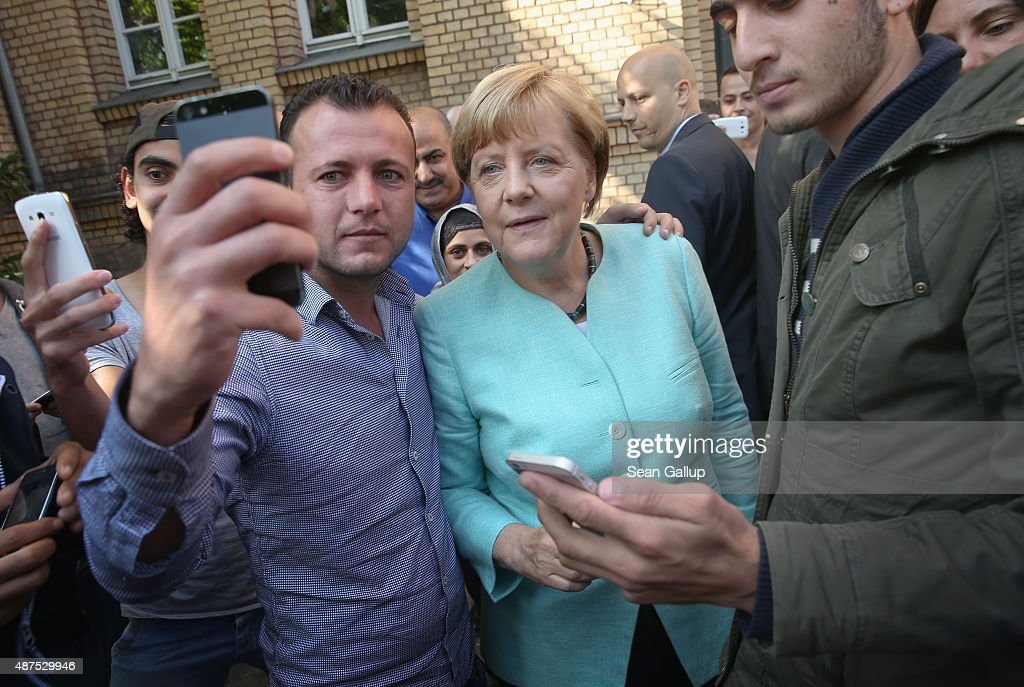 German Chancellor Angela Merkel pauses for a selfie with a migrant before she visited the AWO Refugium Askanierring shelter for migrants on September 10, 2015 in Berlin, Germany. Merkel visited several facilities for migrants today, including an application center for asylum-seekers, a school with welcome classes for migrant children and a migrant shelter. Thousands of migrants are currently arriving in Germany every day, most of them via the Balkans and Austria. Germany is expecting to receive 800,000 asylum applicants this year.