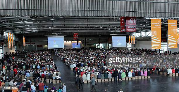German Chancellor Angela Merkel pictured on a giant screen delivers a speech during day 3 of the 2nd Ecumenical Church Day at International Congress...