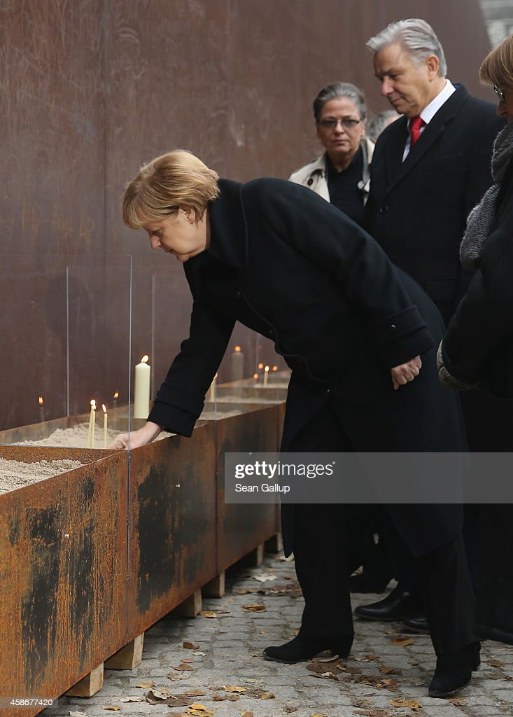 German Chancellor Angela Merkel places a candle as Berlin Mayor Klaus Wowereit looks on at the Berlin Wall Memorial at Bernauer Strasse on the 25th...