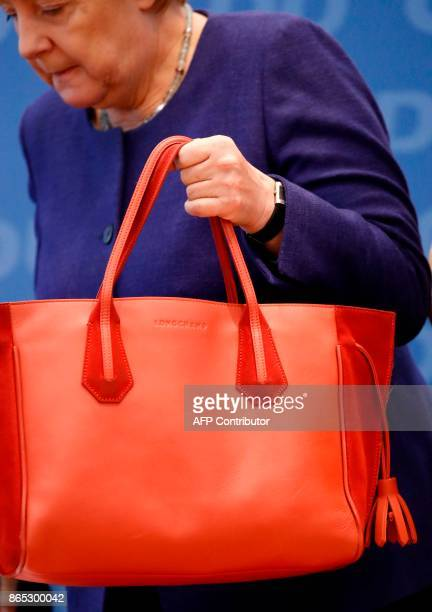 German Chancellor Angela Merkel places her bag as she arrives for a meeting of the federal executive board of the Christian Democratic Union in...