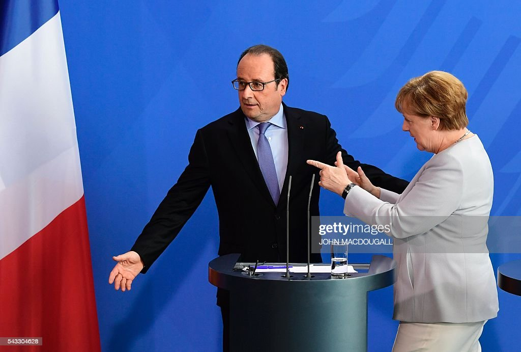 German Chancellor Angela Merkel points the way to French President Francois Hollande (L) after addressing a joint press conference with Italy's Prime Minister ahead of talks following the Brexit referendum at the chancellery in Berlin, on June 27, 2016. Britain's shock decision to leave the EU forces German Chancellor Angela Merkel into the spotlight to save the bloc, but true to her reputation for prudence, she said she would act neither hastily nor nastily. / AFP / John MACDOUGALL