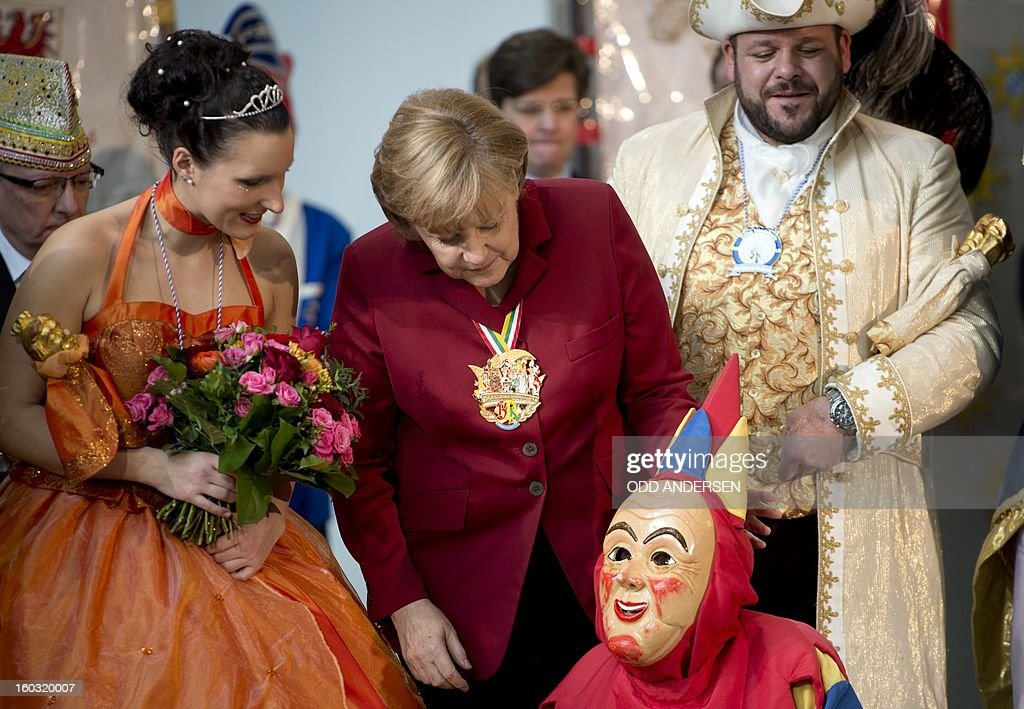 German Chancellor Angela Merkel (C) pose for a picture with Bavarian Carnival Prince Roland (R) and Princess Tanja I (L) and their court jester as she greeted carnival performers from around Germany at the Chancellery in Berlin on January 29, 2013. AFP PHOTO / ODD ANDERSEN