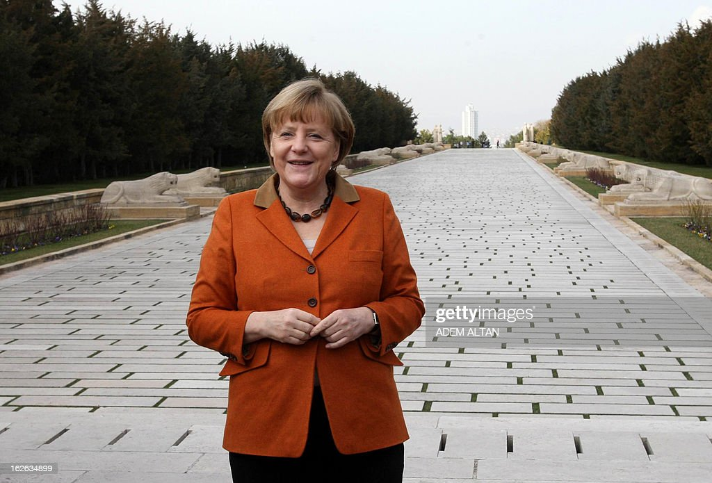 German Chancellor Angela Merkel (C) poses after visiting the mausoleum of Turkey's Republic's founder Kemal Ataturk in Ankara, on February 25, 2013, on the second an final day of her official visit to Turkey. AFP PHOTO ADEM ALTAN