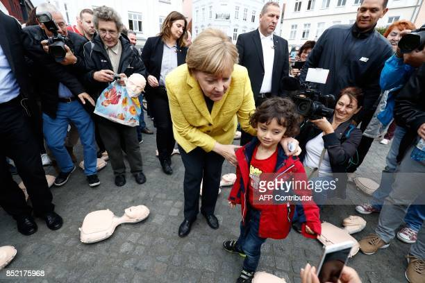 German Chancellor Angela Merkel poses for a picture with a child as she visits a booth of the German Red Cross staging an information campaign on...