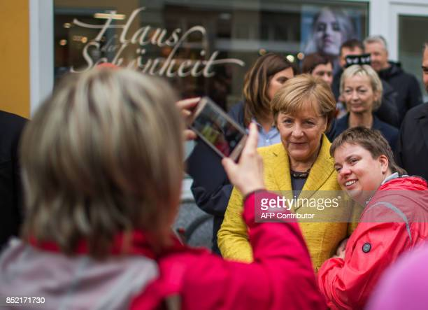 German Chancellor Angela Merkel poses for a picture with wellwishers as she tours the old town of Stralsund northeastern Germany on September 23 one...