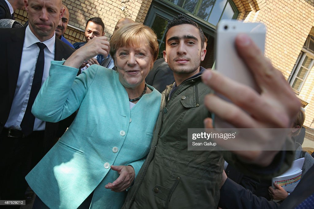 German Chancellor Angela Merkel poses for a selfie with a migrant from Syria after she visited the AWO Refugium Askanierring shelter for migrants on...