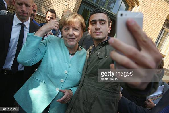 German Chancellor Angela Merkel poses for a selfie with Anas Modamani a refugee from Syria after she visited the AWO Refugium Askanierring shelter...