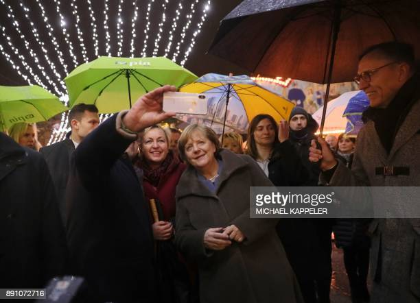 German Chancellor Angela Merkel poses for pictures next to the director of the City eV association KlausJuergen Meier during a visit at the Christmas...