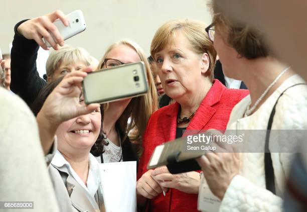 German Chancellor Angela Merkel poses for selfies at the conclusion of an event to commend volunteers who are helping refugees and migrants on April...