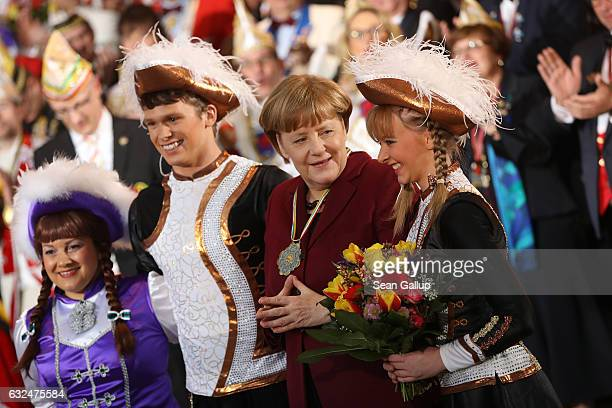 German Chancellor Angela Merkel poses with Carnival performers during the annual Carnival reception at the Chancellery on January 23 2017 in Berlin...