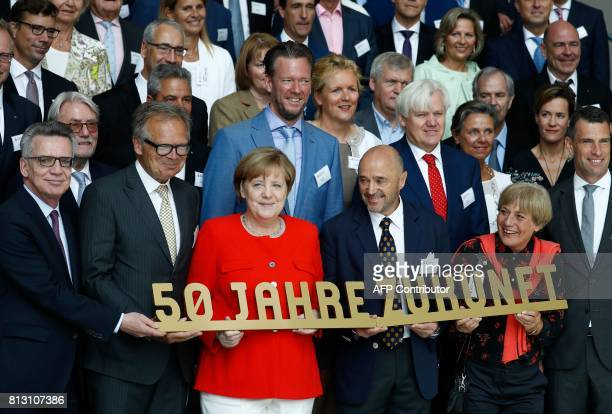 German Chancellor Angela Merkel poses with German Interior Minister Thomas de Maiziere the supervisory board chairman of the Deutsche Sporthilfe...