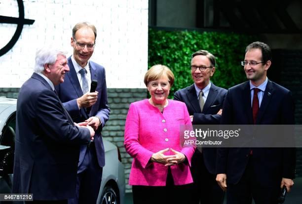German Chancellor Angela Merkel poses with Michael Lohscheller CEO of Opel Opel's CFO Philippe de Rovira the president of the German Automobile...