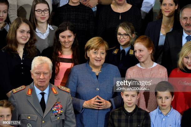 German Chancellor Angela Merkel poses with relatives and children of German Bundeswehr soldiers serving abroad on December 12 2017 at the Chancellery...