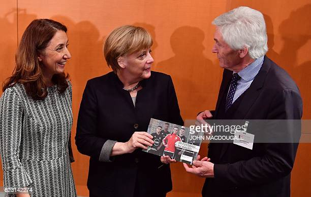 German Chancellor Angela Merkel poses with vice president of the German footbal association Eugen Gehlenborg and Germany's commissioner for migrants...