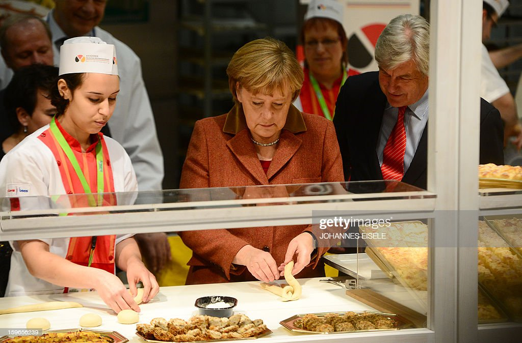 German Chancellor Angela Merkel (C) prepares a bread at the German bakery academy booth as she opens the Gruene Woche Agricultural Fair in Berlin on January 18, 2013. This year the official partner country of the fair is The Netherlands. EISELE