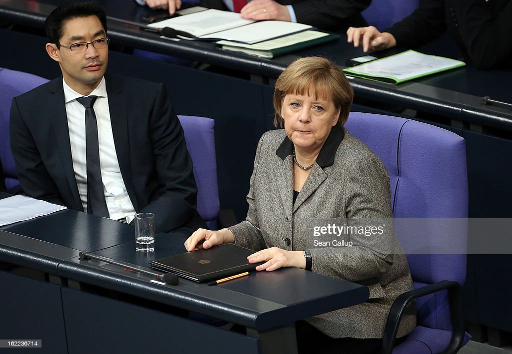 German Chancellor <a gi-track='captionPersonalityLinkClicked' href=/galleries/search?phrase=Angela+Merkel&family=editorial&specificpeople=202161 ng-click='$event.stopPropagation()'>Angela Merkel</a> prepares to give a government declaration on the forthcoming European Union budget that was agreed upon at a summit in Brussels recently as German Vice Chancellor and Economy Minister <a gi-track='captionPersonalityLinkClicked' href=/galleries/search?phrase=Philipp+Roesler&family=editorial&specificpeople=4838791 ng-click='$event.stopPropagation()'>Philipp Roesler</a> looks on on February 21, 2013 in Berlin, Germany. The budget required wrangling and compromises and will give more money to economically-stricken member state.