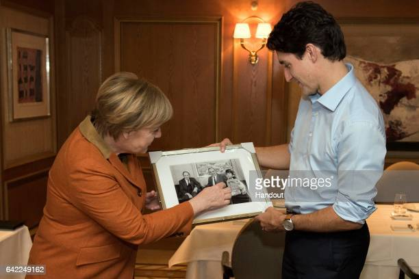 German Chancellor Angela Merkel presents a photo to Canadian Prime Minister Justin Trudeau which shows him posing with his father Pierre Trudeau the...