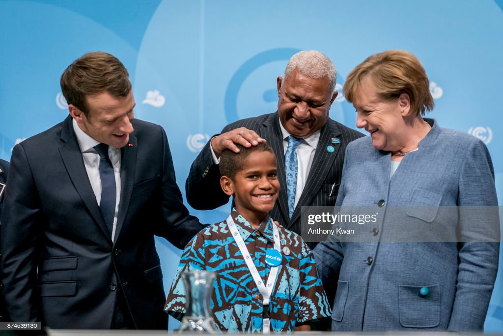 German Chancellor Angela Merkel, Prime Minister of Fiji Frank Bainimarama, (C) and French President Emmanuel Macron (L) pose with a young man for a photograph during the COP 23 United Nations Climate Change Conference on November 15, 2017 in Bonn, Germany. The conference, which ends on November 17, has brought together 25,000 participants to discuss climate change-related issues and the progress signatory members are making towards fulfilling CO2 and other pollutants reductions. Many signatories of the Paris Agreement are failing to fulfill their commitments towards combating the global temperature rise. Recent data shows that global CO2 levels are again rising after having stagnated the last couple of years.
