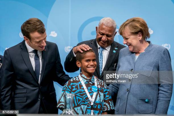 German Chancellor Angela Merkel Prime Minister of Fiji Frank Bainimarama and French President Emmanuel Macron pose with a young man for a photograph...