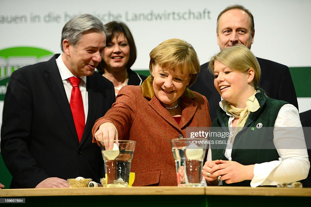 German Chancellor Angela Merkel (C) puts an egg into a glas of water next to Berlin Mayor Klaus Wowereit (L) at booth as she opens the Gruene Woche Agricultural Fair in Berlin on January 18, 2013. This year the official partner country of the fair is The Netherlands. EISELE