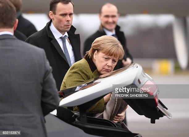 German Chancellor Angela Merkel puts her coat in the trunk of a car upon arrival at Arlanda Airport outside Stockholm Sweden on January 31 2017...