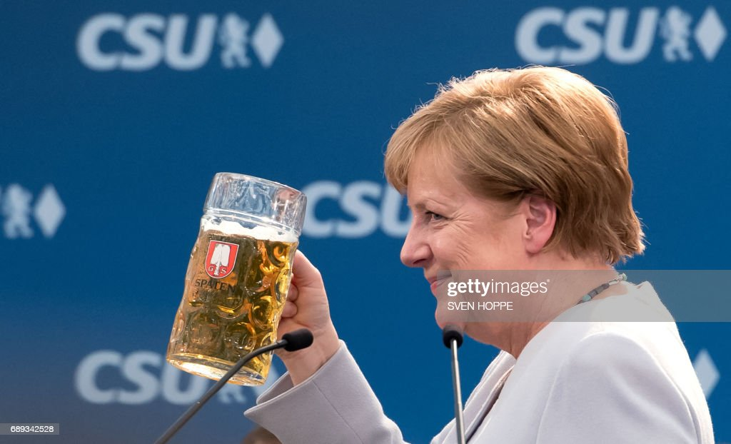 German Chancellor Angela Merkel raises a glass of beer after delivering a speech during a joint campaigning event of the Christian Democratic Union (CDU) and the Christion Social Union (CSU) in Munich, southern Germany, on May 27, 2017. / AFP PHOTO / dpa / Sven Hoppe
