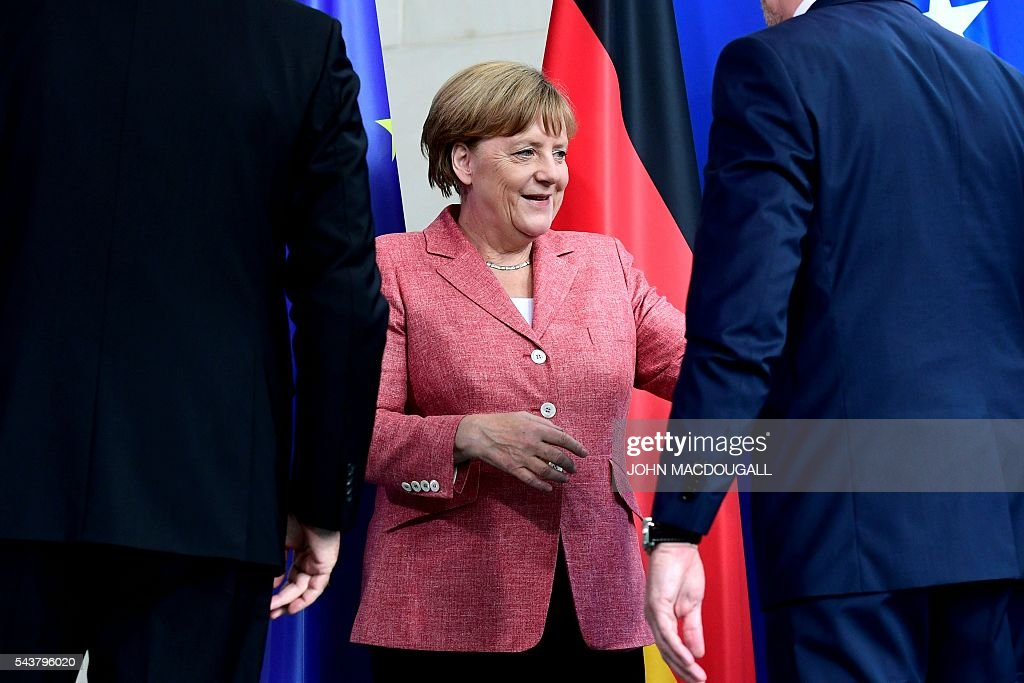 German Chancellor Angela Merkel (C) reacts after a joint press conference with the three members of the Presidency of Bosnia and Herzegovina Bakir Izetbegovic (R), Dragan Covic (L) and Mladen Ivanic (unseen) at the chancellery in Berlin on June 30, 2016. / AFP / John MACDOUGALL