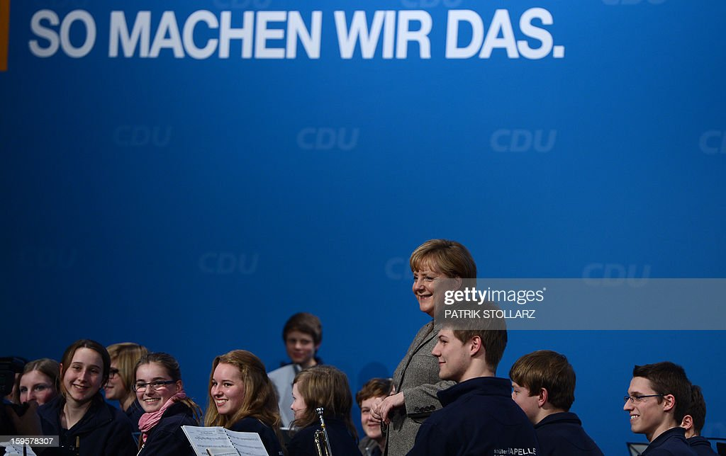 German Chancellor Angela Merkel (C) reacts next to a youth orchestra in front of a placard saying 'we do it like this' after a speech during an election campaign event of the regional Christian Democratic Union (CDU) party for the 2013 state elections in Osnabrueck, northern Germany, on January 16, 2013.