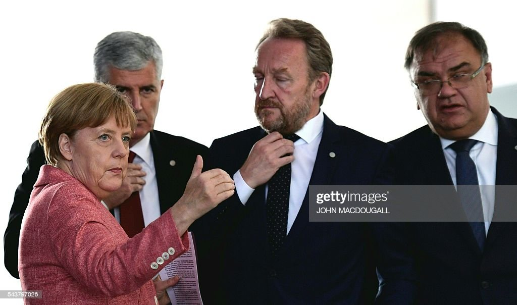 German Chancellor Angela Merkel (L) reacts prior to a joint press conference with the three members of the Presidency of Bosnia and Herzegovina, Bakir Izetbegovic (2nd R), Dragan Covic (2nd L) and Mladen Ivanic (R) after talks at the chancellery in Berlin on June 30, 2016. / AFP / John MACDOUGALL