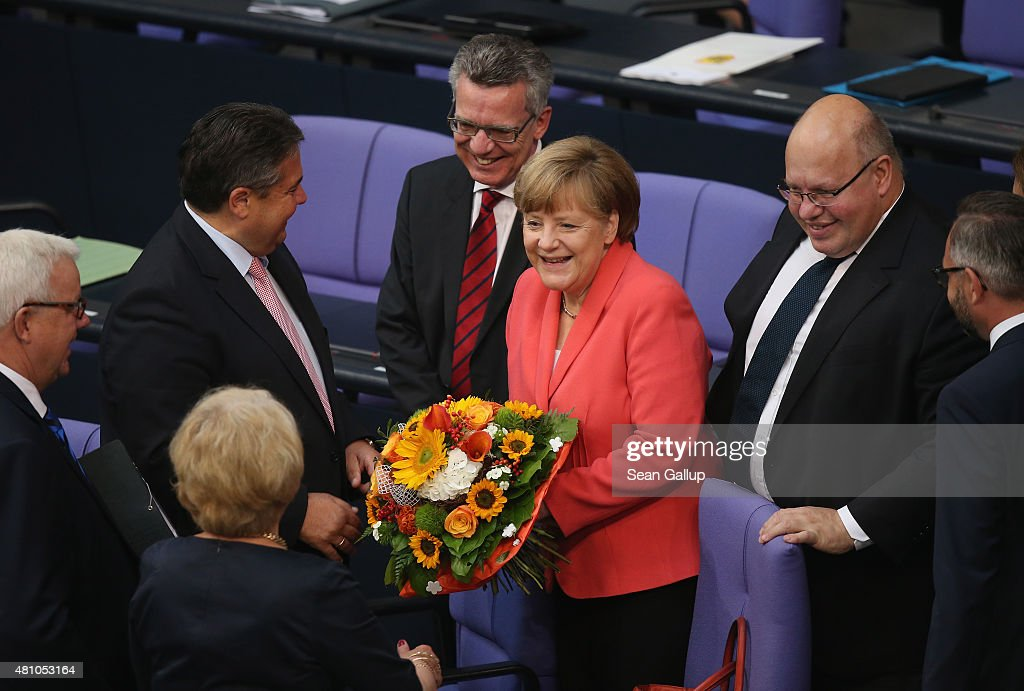 German Chancellor Angela Merkel receives flowers and congratulations on her birthday prior to debates and votes over the third EU financial aid package to Greece at an extraordinary session of the German parliament, the Bundestag, on July 17, 2015 in Berlin, Germany. The Bundestag is among several European parliaments that must vote on whether to allow negotations over the aid package that will help Greece to avert state bankruptcy and shore up the Greek banking system.