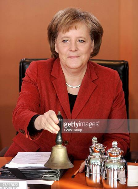 German Chancellor Angela Merkel rings a bell to begin the weekly German government cabinet meeting at the Chancellery February 7 2007 in Berlin...