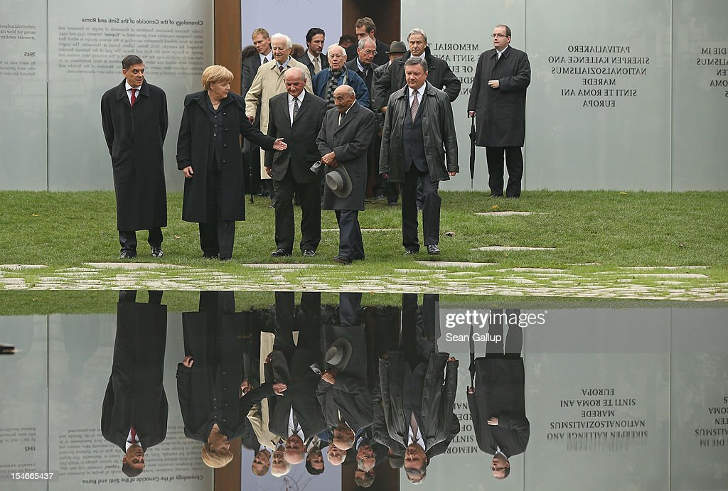 """German Chancellor <a gi-track='captionPersonalityLinkClicked' href=/galleries/search?phrase=Angela+Merkel&family=editorial&specificpeople=202161 ng-click='$event.stopPropagation()'>Angela Merkel</a> (C), Romani Rose (L), Chairman of the Central Council of Sinti and Roma in Germany, and Roma Holocaust survivor Reinhard Florian (R) arrive at the """"Memorial to the Sinti and Roma of Europe Murdered Under National Socialism"""" during its inauguration on October 24, 2012 in Berlin, Germany. In addition to targeting Jews during the Holocaust, Hitler also sought to exterminate the Roma population in Europe and estimates of the number killed range from 220,000 to 1,500,000."""