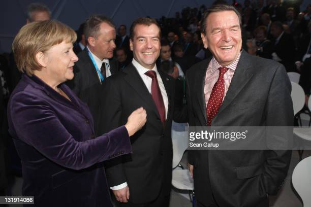 German Chancellor Angela Merkel Russian President Dmitry Medvedev and former German Chancellor Gerhard Schroeder arrive for a ceremony to inaugurate...