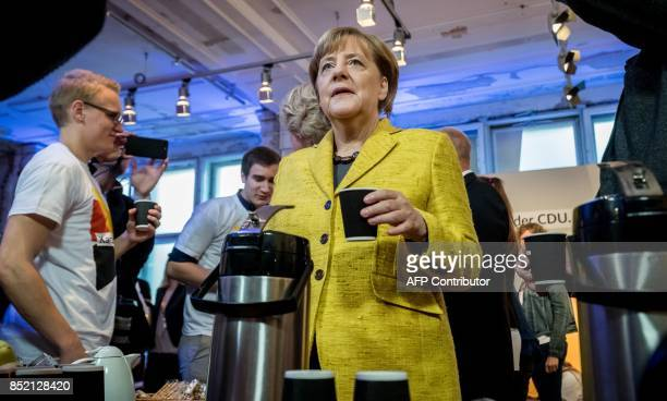 German Chancellor Angela Merkel serves coffee to members of her election campaign team at her conservative Christian Democratic Union party's...
