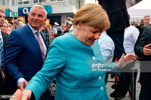German Chancellor Angela Merkel shakes hands as she arrives to address an election campaign rally of the Christian Democratic Union in Heilbronn...