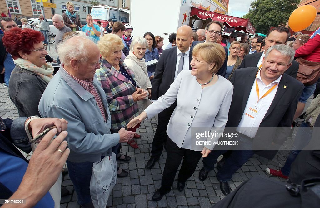 German Chancellor Angela Merkel shakes hands with a resident as she visits a street market in RibnitzDamgarten eastern Germany during her campaign...