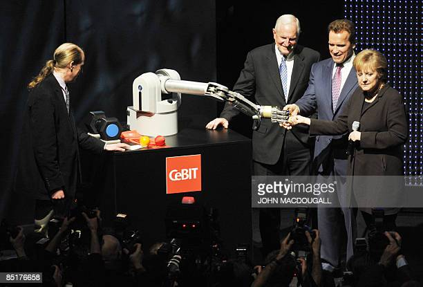 German Chancellor Angela Merkel shakes hands with a robotic arm as California Governor Arnold Schwarzenegger and CEO of Intel Greg Barett look on...